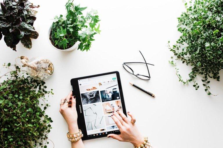 Es ist ein Tablet zu sehen, das auf einem Tisch liegt und Frauenhände scrollen. Auf dem Tisch sind außerdem Pflanzen, eine Brille und ein Stift zu sehen