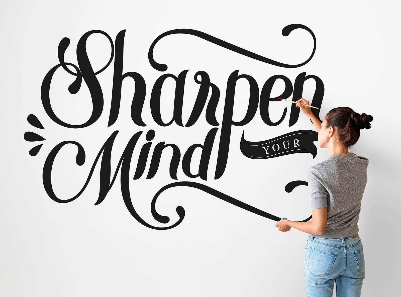 """Es ist eine Frau abgebildet, die an einer Wand den Schriftzug """"Sharpen your mind"""" in scharzer Schrift malt"""