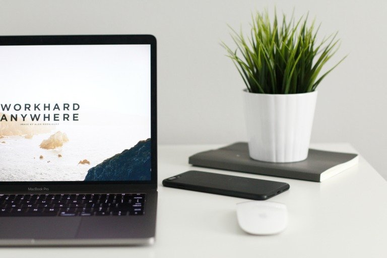 """Website erstellen lassen: Auf einem Tisch stehen ein Laptop, eine weiße Maus, Handy und eine Pflanze, die auf einem Notizbuch steht. Auf dem Laptopbildschirm ist der Schriftzug """"Workhardanywhere"""" zu sehen"""